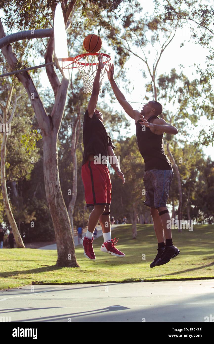 Dos hombres jóvenes dispara aros de baloncesto en el parque al atardecer Imagen De Stock