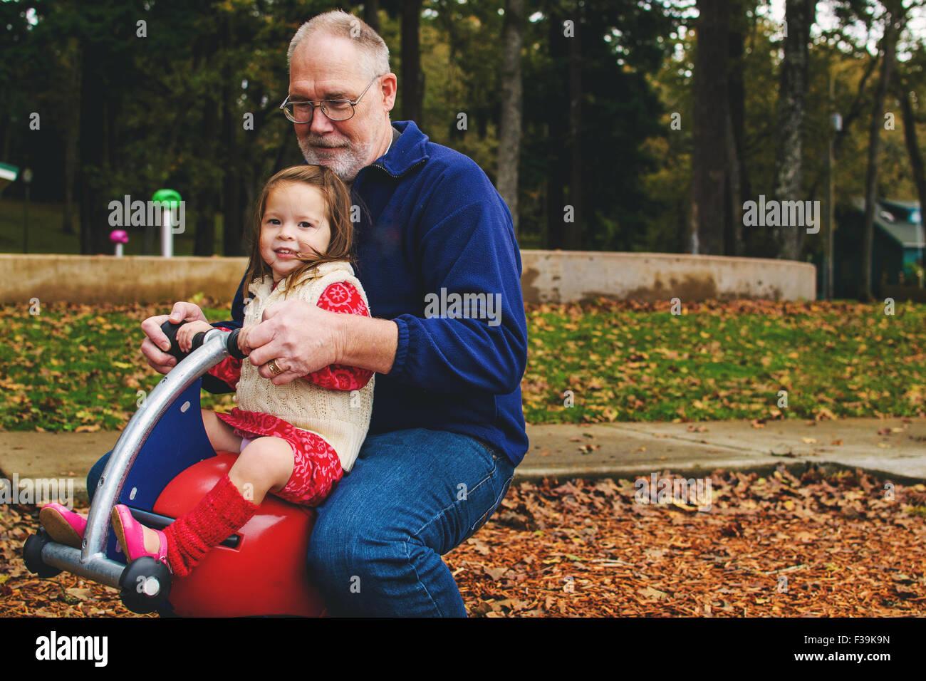 Niña jugando con su abuelo en el parque Foto de stock