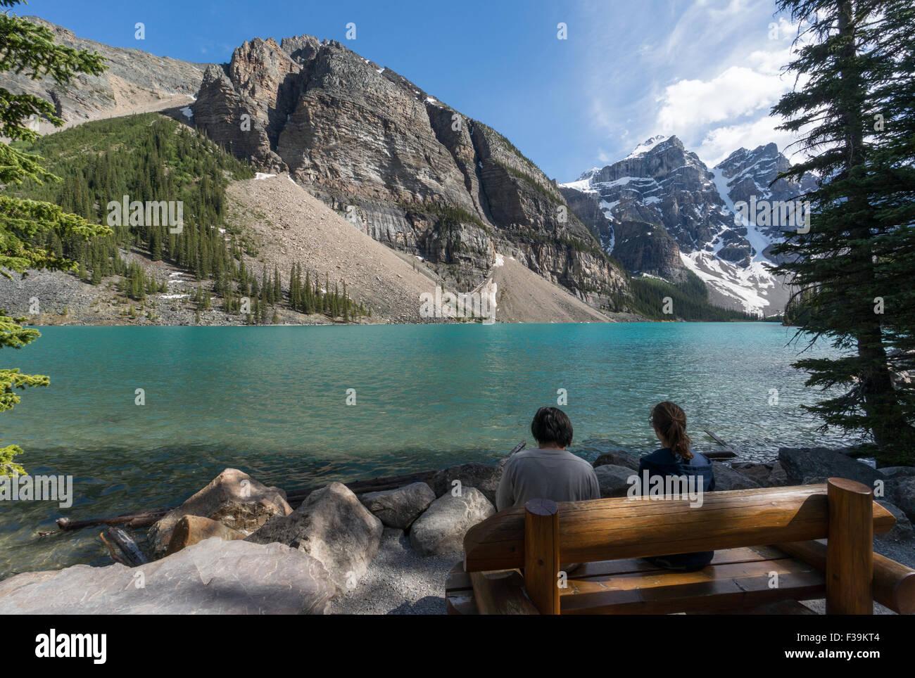 Dos personas sentadas por el Lago Moraine, el Parque Nacional Banff, Canadian Rockies, Alberta, Canadá Imagen De Stock