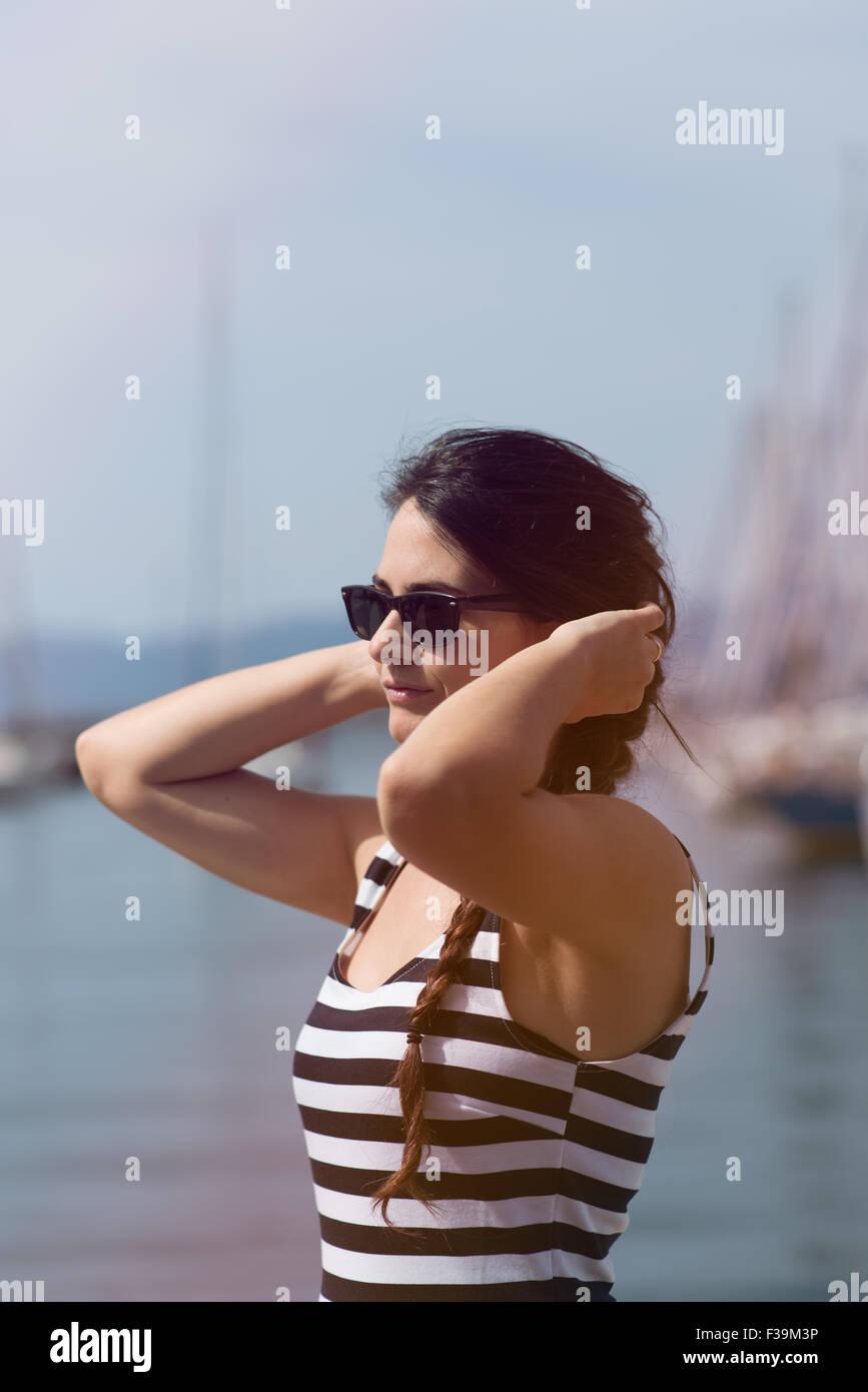Retrato de una joven mujer sosteniendo sus manos a las orejas. Imagen De Stock
