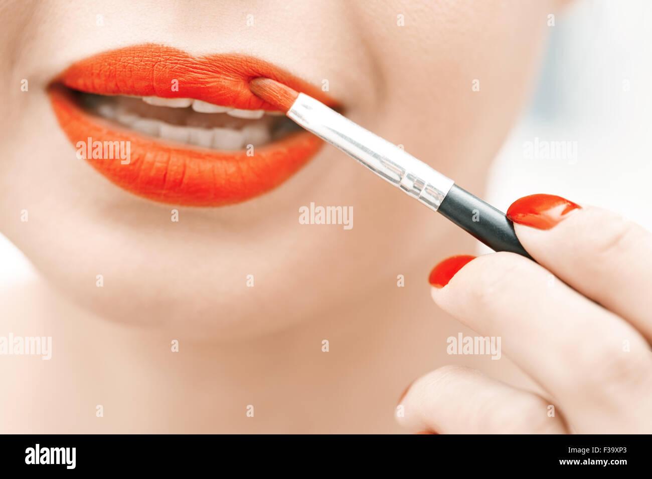 Mujer aplicar lápiz labial rojo. Vista cercana en la cara Imagen De Stock