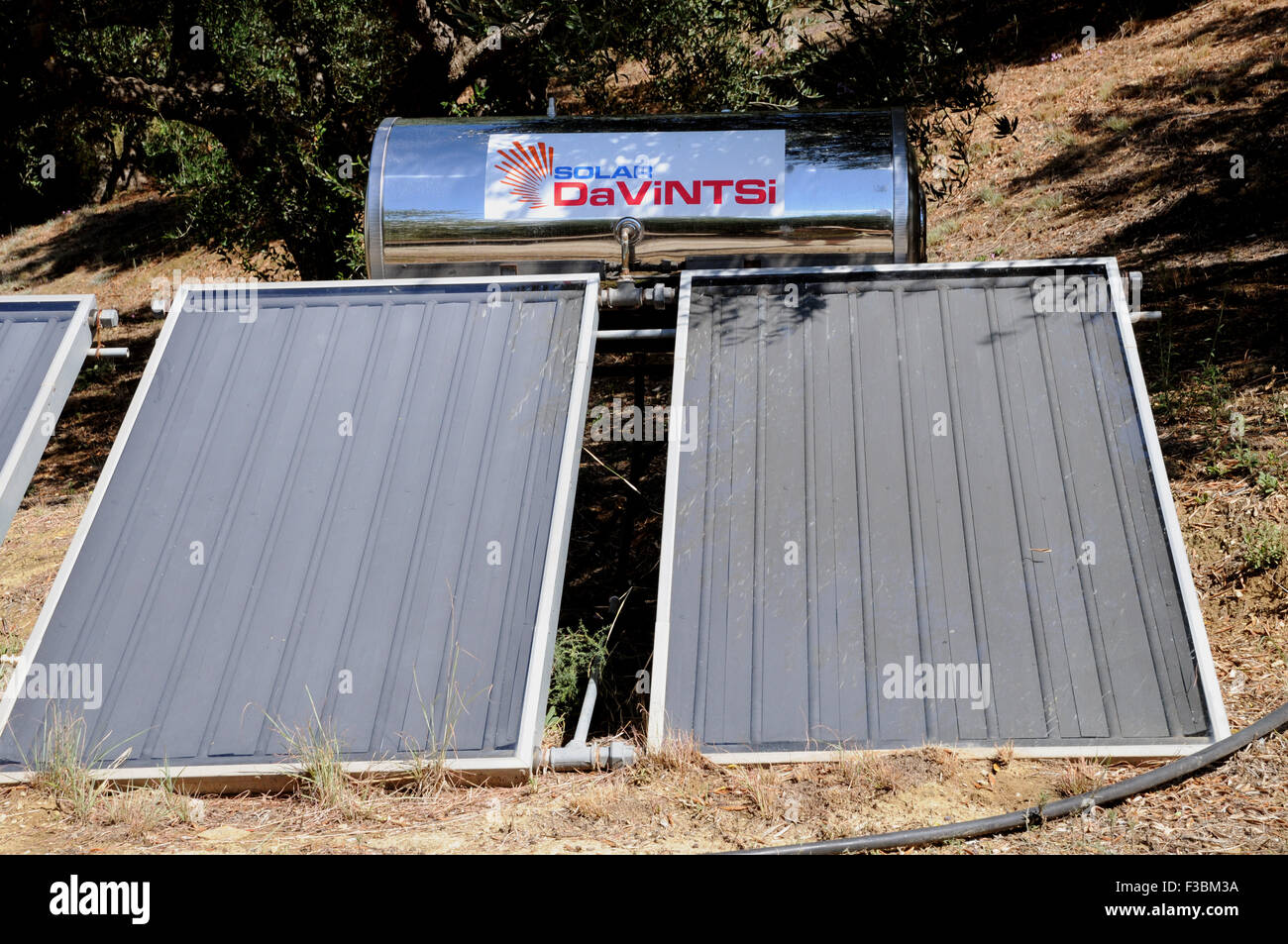 Calentadores solares de agua en el suelo, junto a una casa en la pequeña aldea de Giolova griego en el Peloponeso. Imagen De Stock