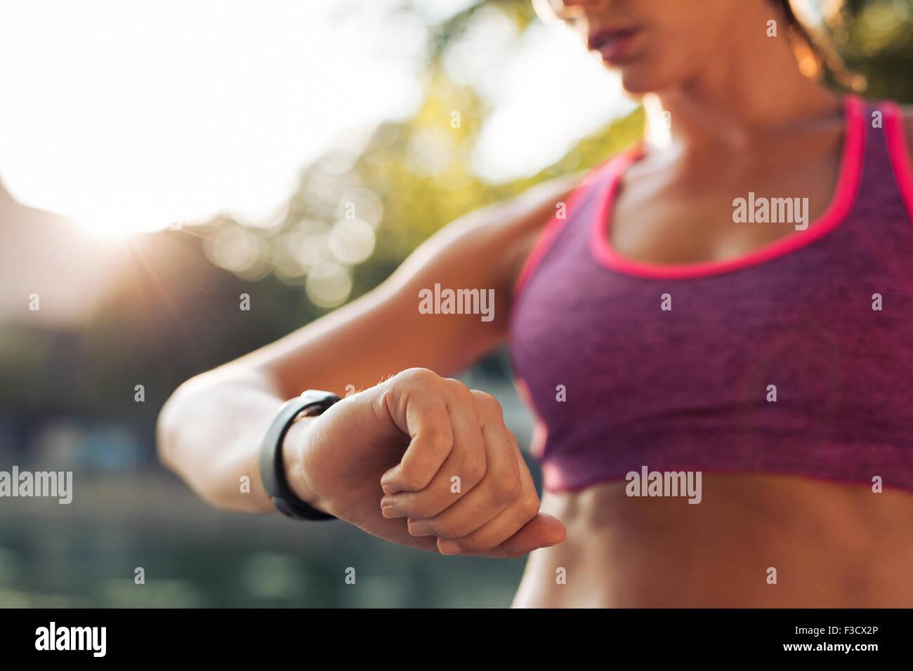 Fitness joven mujer mirando su reloj inteligente mientras toma un descanso en el entrenamiento deportivo. Control Imagen De Stock