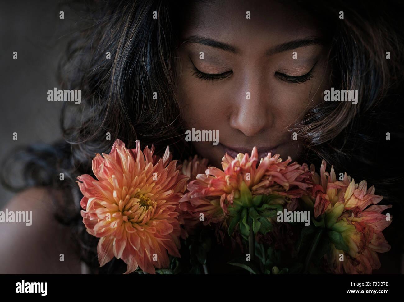 Mujer joven oler las flores Imagen De Stock