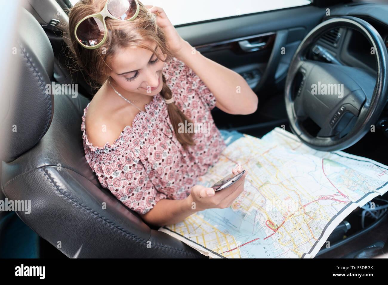 Comprobación de la mujer teléfono en coche con el mapa en la vuelta Imagen De Stock
