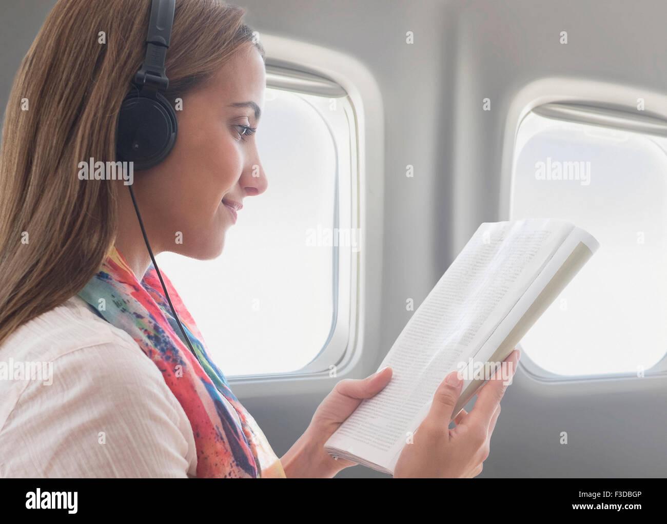 Mujer joven con los auriculares puestos mientras lee un libro sobre avión Foto de stock