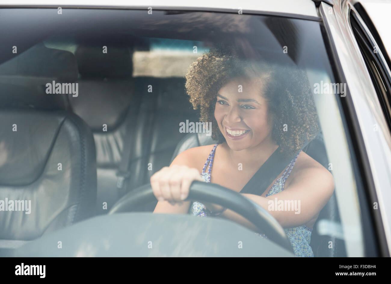 Mujer joven sonriente mientras la conducción de automóviles Imagen De Stock