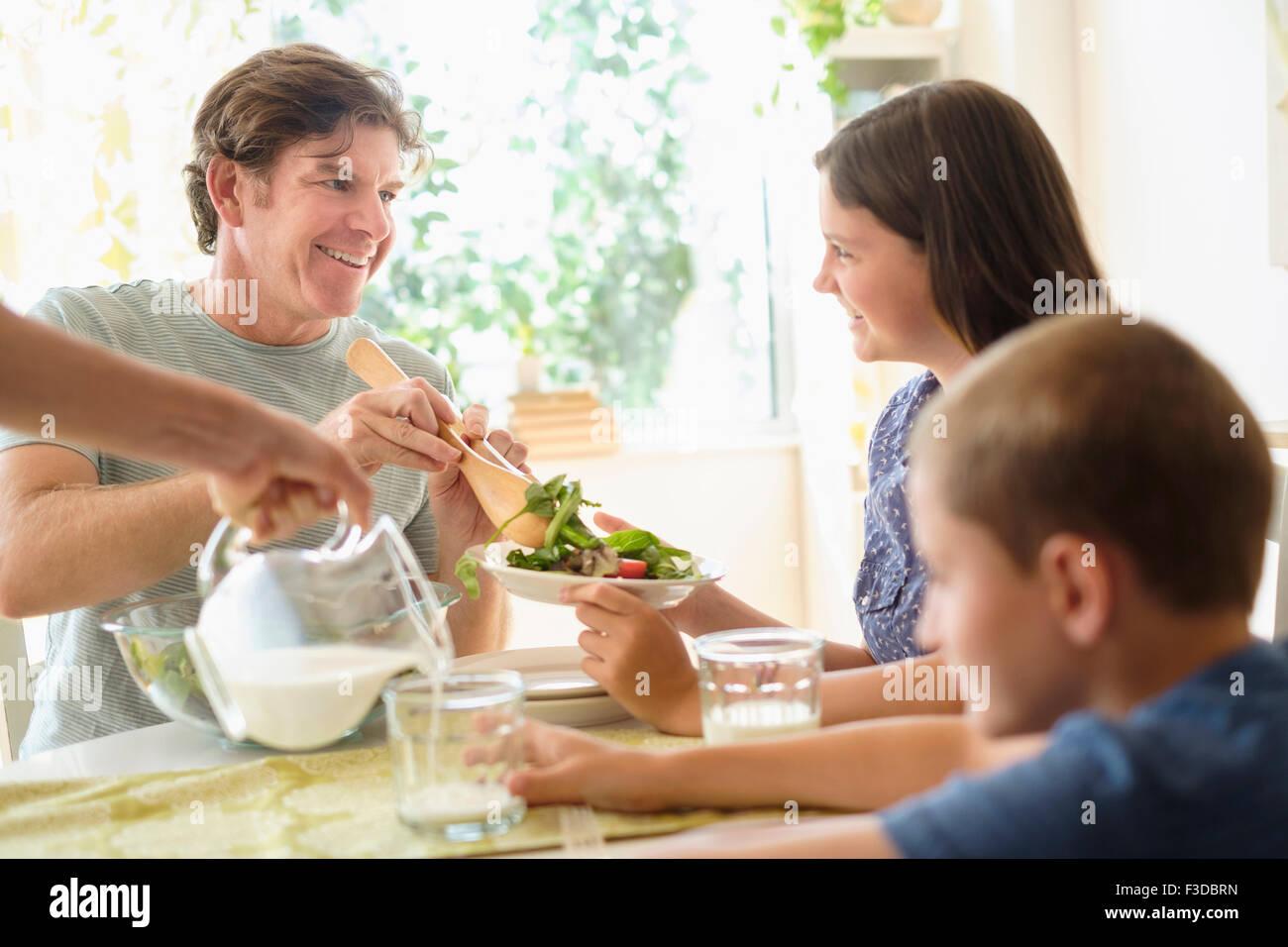 Niños (8-9, 10-11) comer ensalada con padres Imagen De Stock