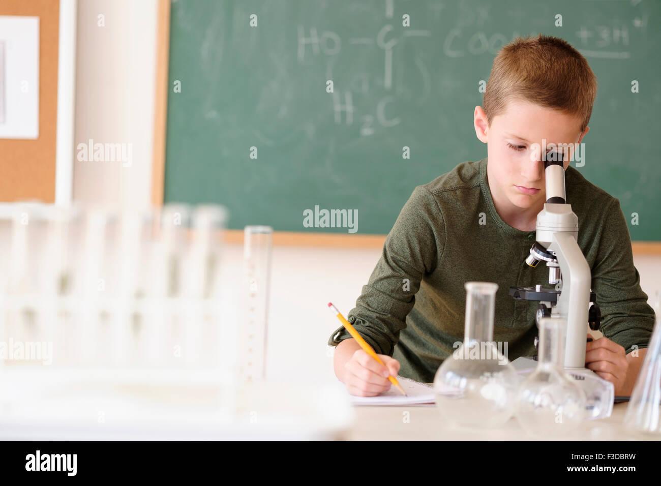 Boy (8-9) mirando a través de microscopio Imagen De Stock