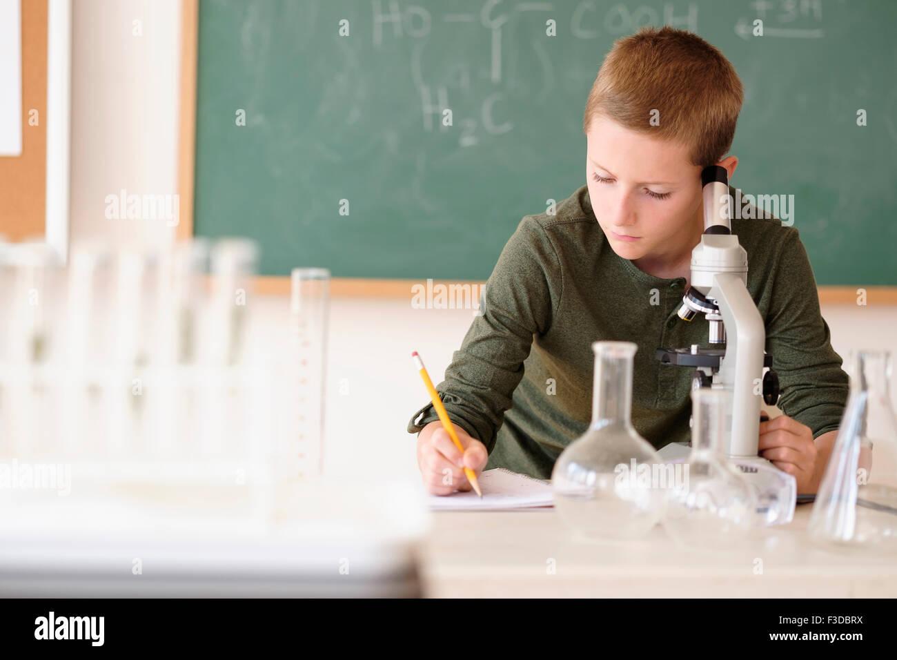 Boy (8-9) tomando notas en el aula Imagen De Stock