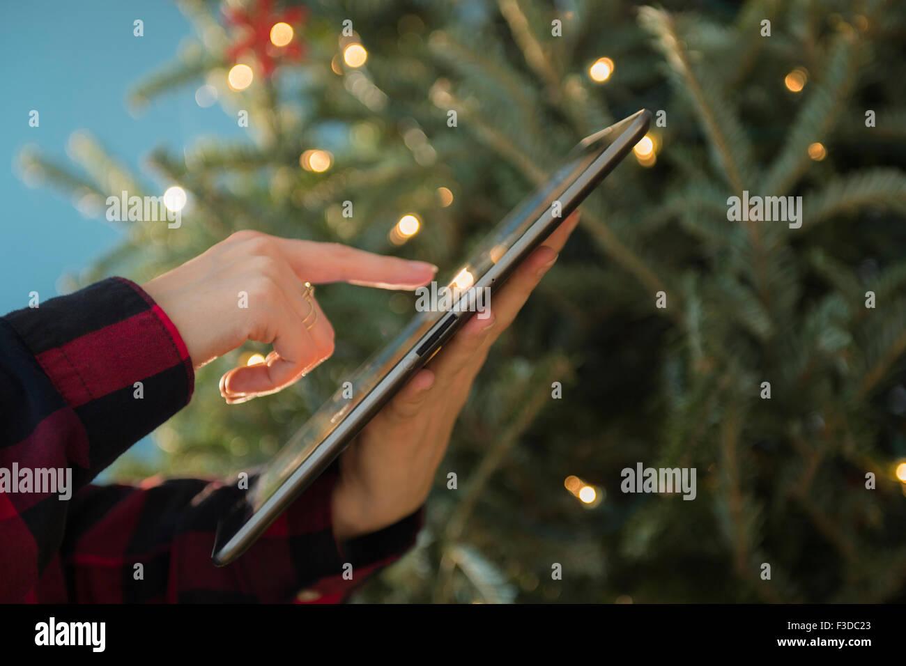 La persona utilizando tablet cerca del árbol de Navidad Imagen De Stock