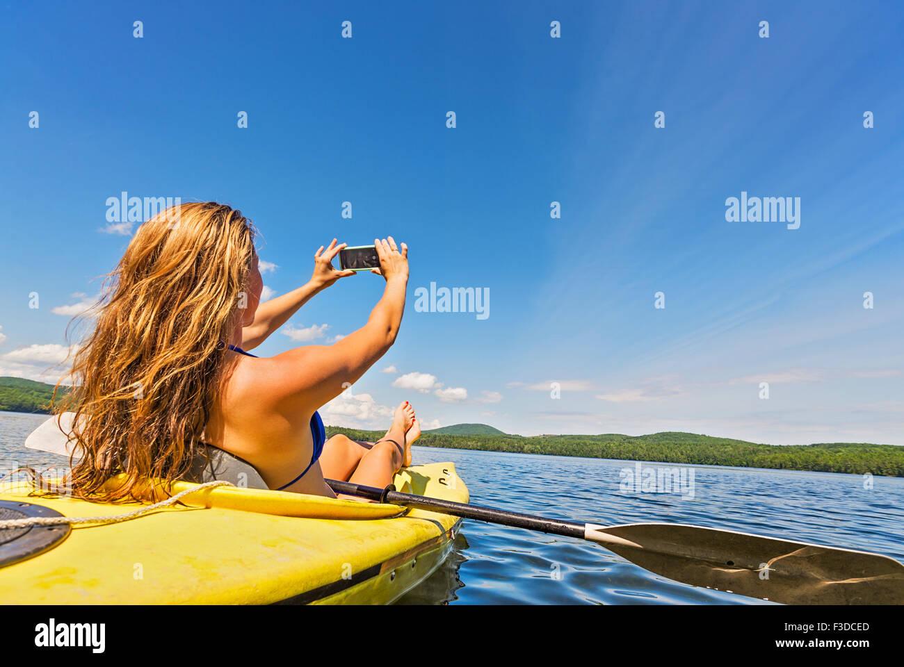 Mujer joven tomando selfie en kayak en el lago Foto de stock