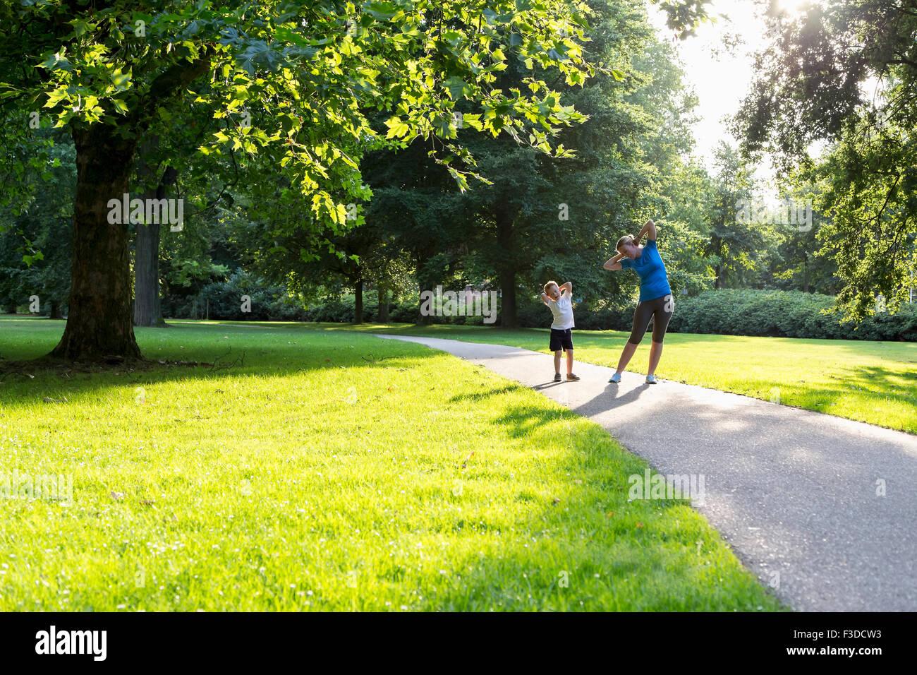 Madre e hijo (12-13) ejerciendo en estacionamiento Imagen De Stock
