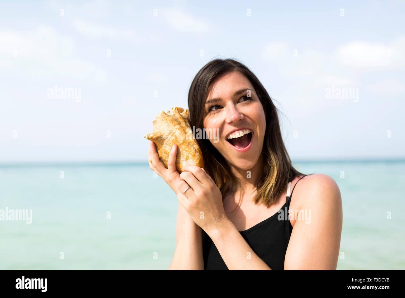 Mujer escuchando seashell Imagen De Stock