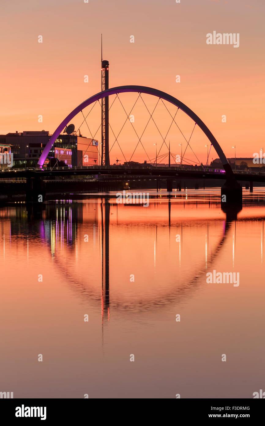 El Clyde Arc Puente reflejado en el río Clyde en el atardecer, Glasgow, Escocia, Reino Unido Foto de stock