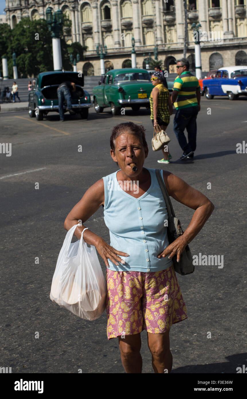 Una mujer local representa las manos en las caderas con sus compras de fumar un cigarro cubano sonriente en La Habana, la capital de la República de Cuba Foto de stock