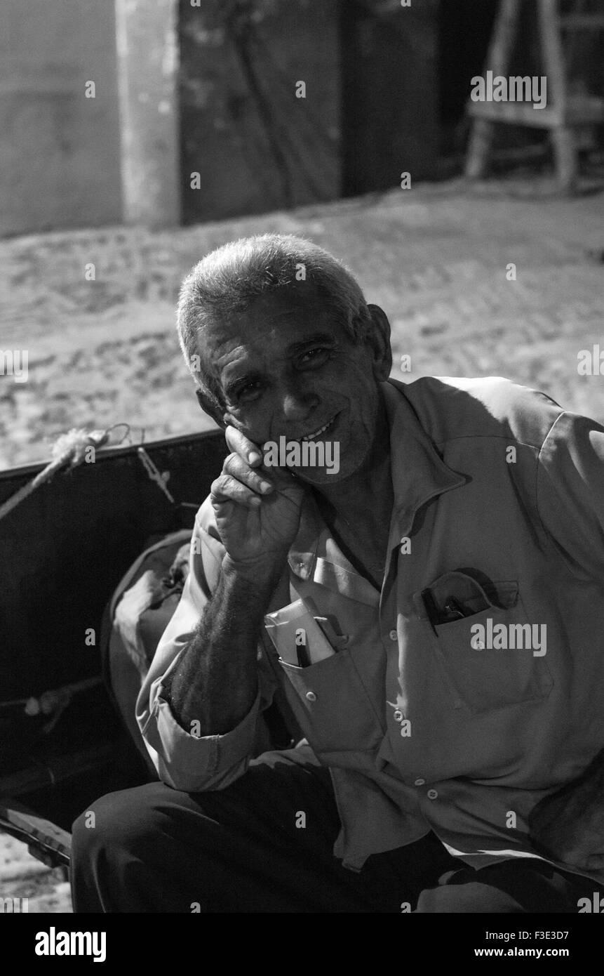 Retrato en blanco y negro de un hombre bien vestido local está sonriendo en la calle en Trinidad, una ciudad en el centro de Cuba. Foto de stock