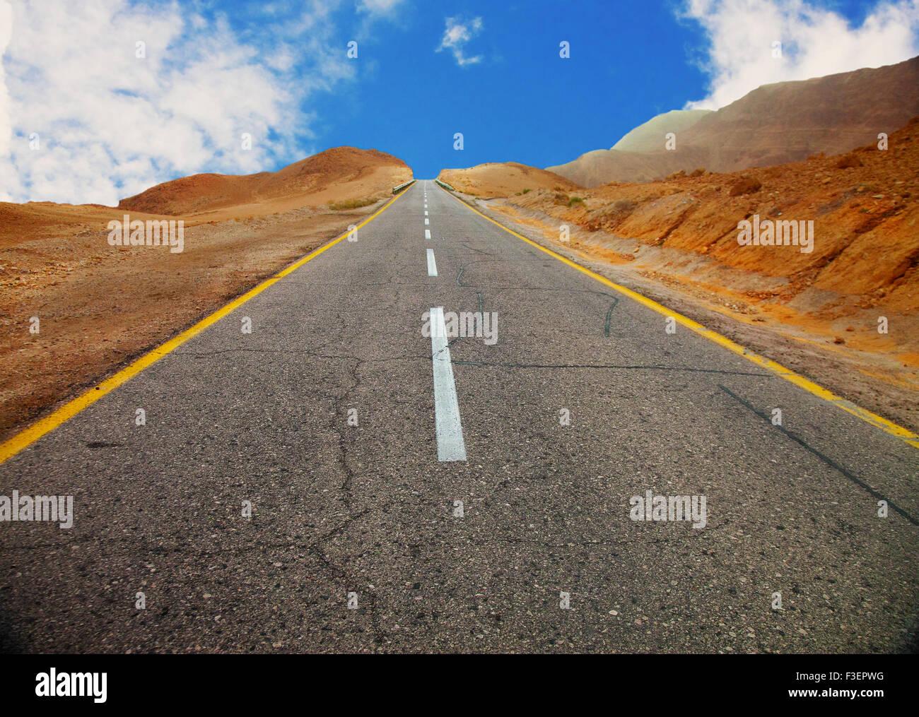 Un fragmento de la vieja carretera de asfalto entre colinas desérticas antes del atardecer (con efecto de vignette) Imagen De Stock