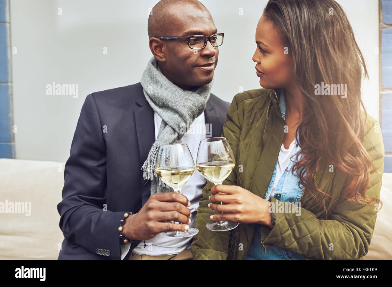 Amorosa pareja americana africana en un abrazo tostado mutuamente con vino blanco, tal y como se ven profundamente Imagen De Stock