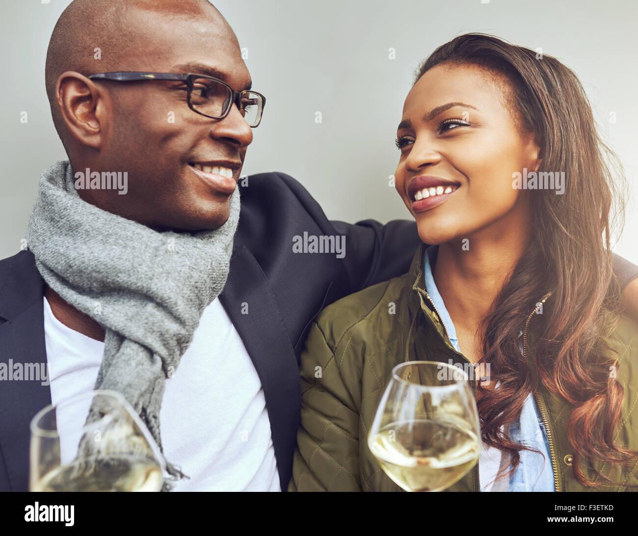 Romántica pareja joven afroamericano sentado disfrutando del brazo vasos de vino blanco y sonriendo amorosamente Imagen De Stock