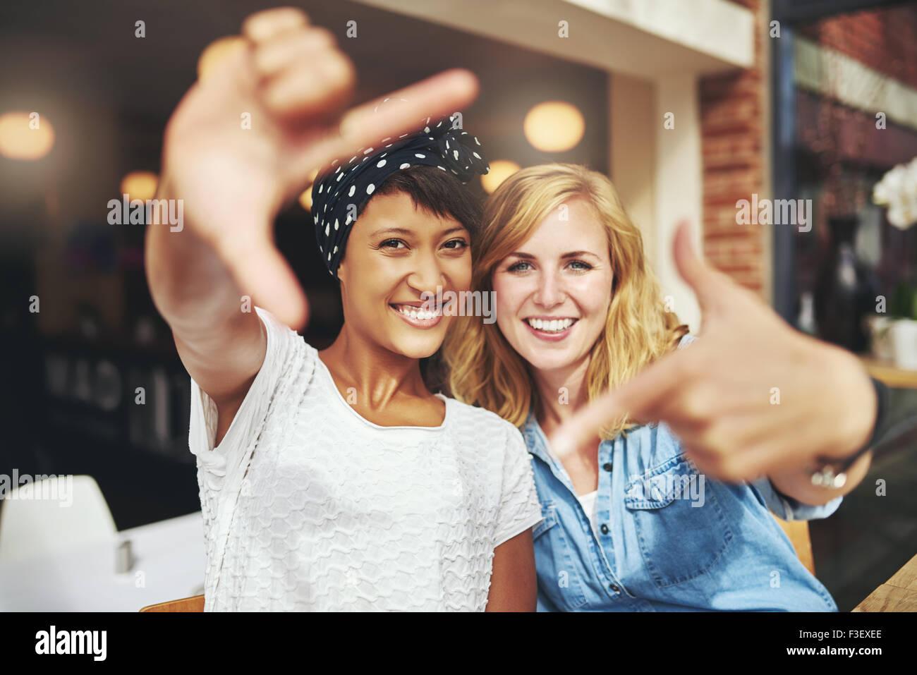 Diversión señoritas enmarcar sus caras con sus dedos en un autorretrato creativo mientras se sientan juntos Imagen De Stock