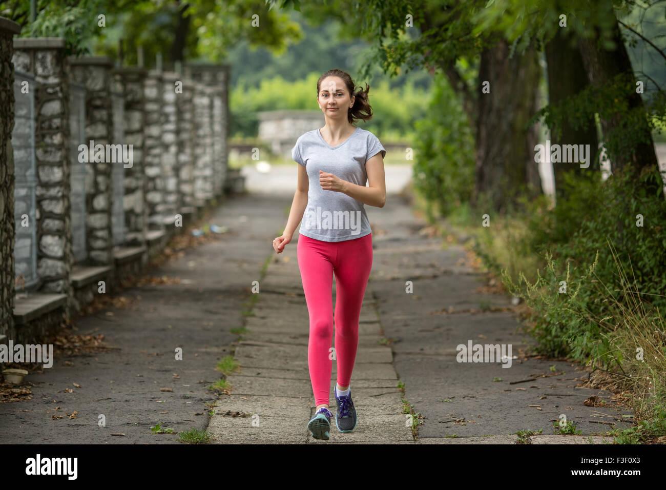 Deportes joven chica durante un jogging en el parque. Ejecutando, estilo de vida saludable. Imagen De Stock