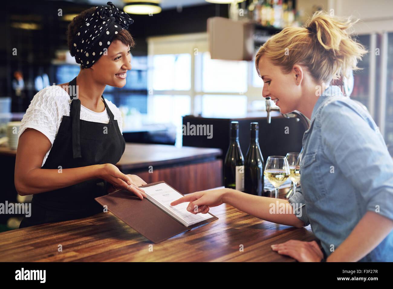 Clienta elegir vino a partir de una lista de vinos presentados a ella por una encantadora joven afroamericano camarero Imagen De Stock