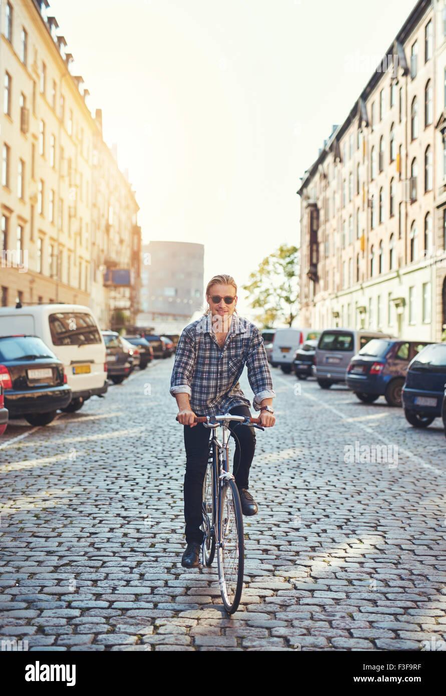 El hombre monta su bicicleta por la ciudad, sonriendo a la cámara con un aspecto atractivo Imagen De Stock