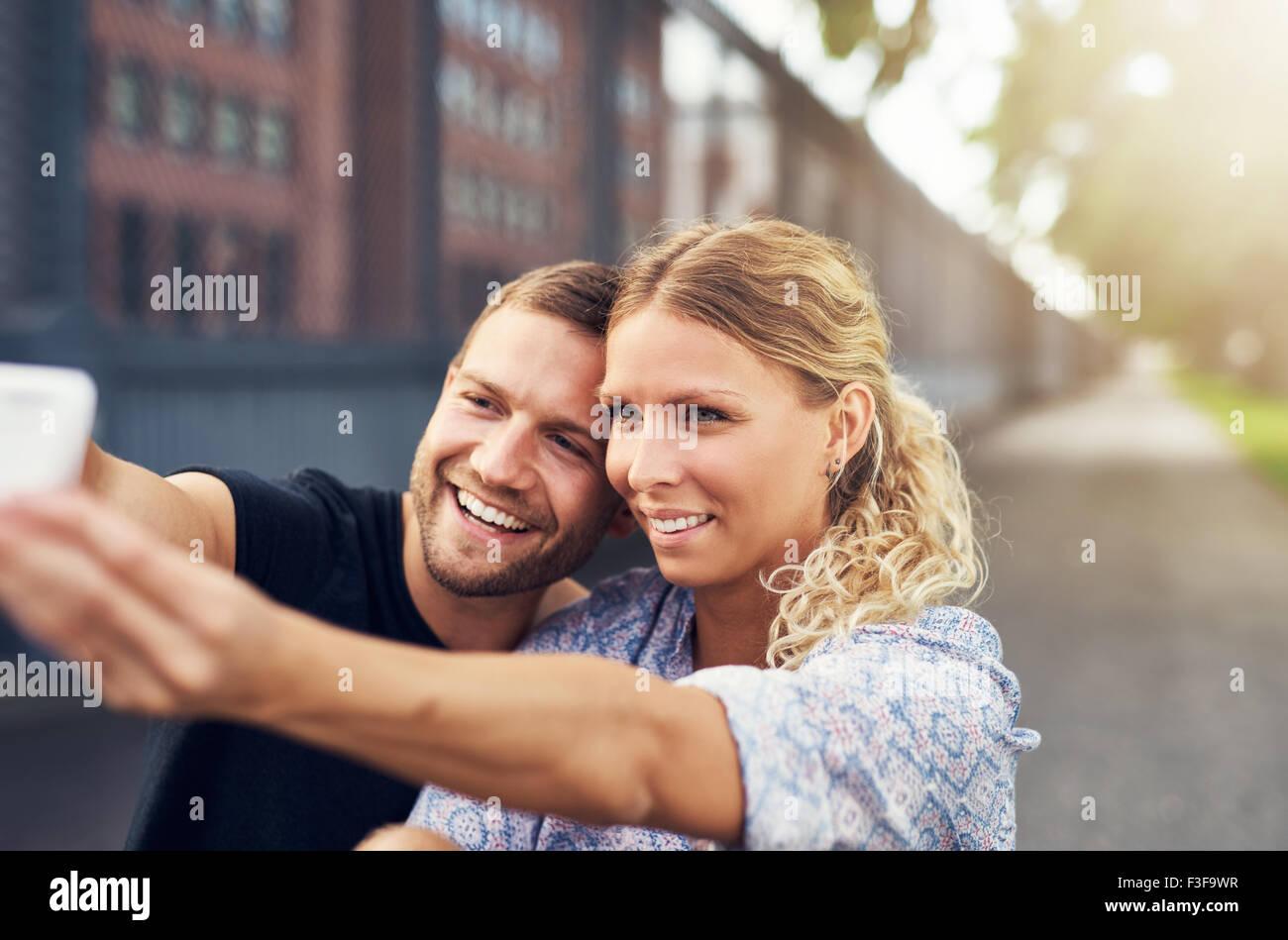 Hermosa pareja teniendo un selfie mientras está sentado en un parque Imagen De Stock