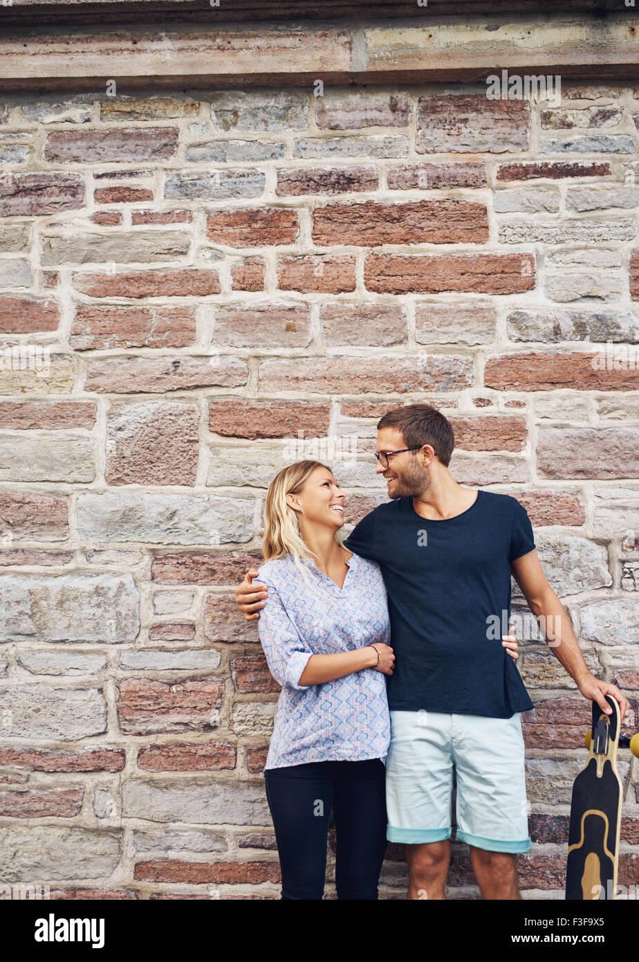 Disparo de tres cuartos de un dulce pareja feliz con el monopatín, sonriendo a uno y otro contra el muro de Imagen De Stock