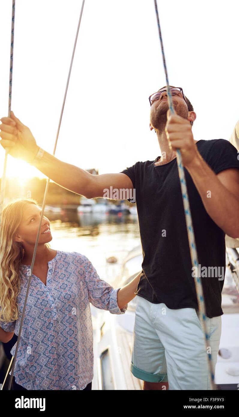 El hombre controlar barco mientras mujer mirando, día de verano Imagen De Stock