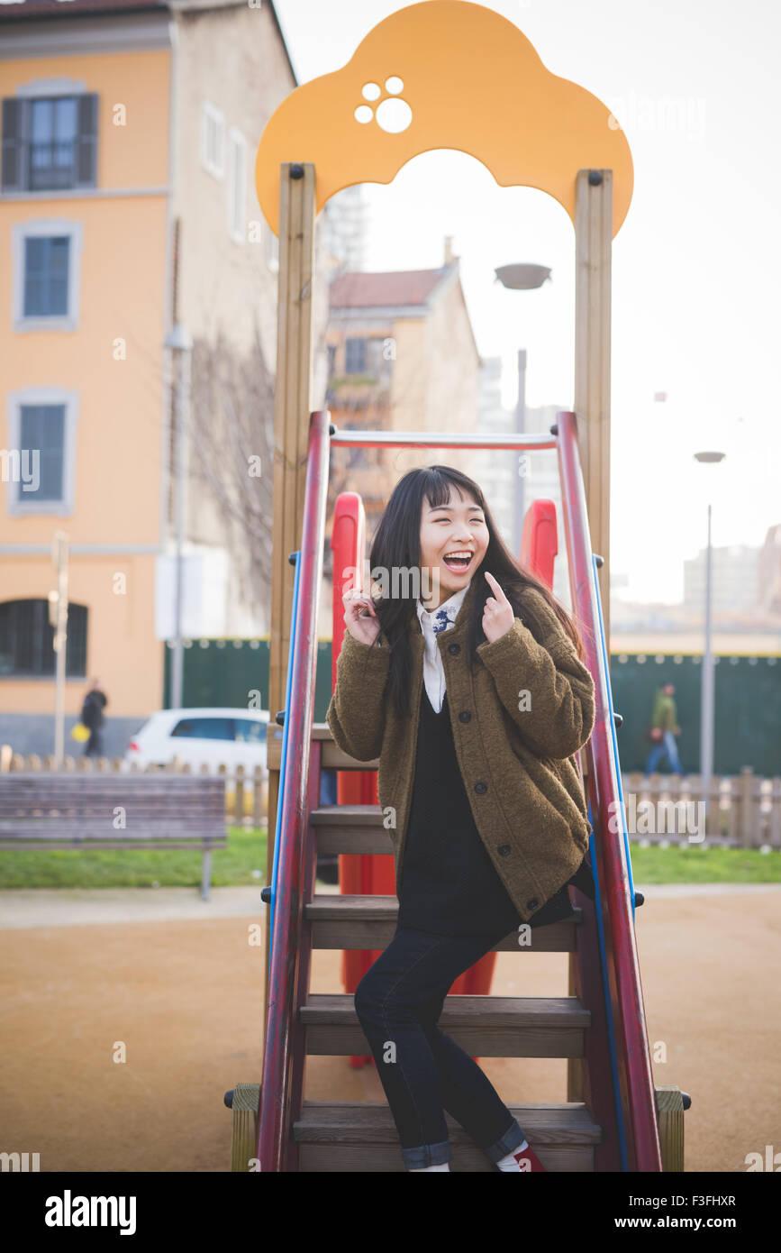 Joven bella asiática marrón largo pelo lacio hipster mujer jugando en un patio de recreo, mirando hacia la izquierda, Foto de stock