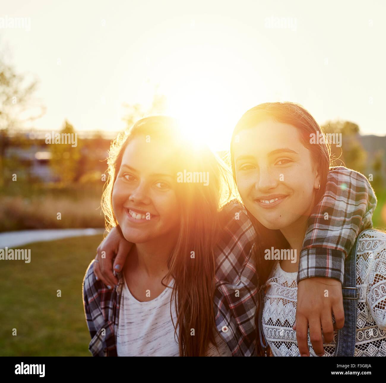 Dos chicas adolescentes fuera en una noche de verano en sun flare Imagen De Stock
