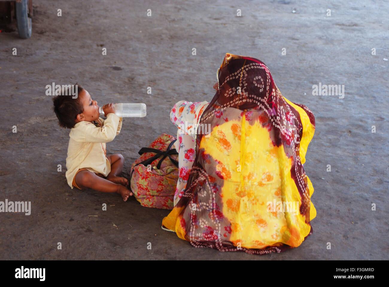 Un niño calmar la sed en el andén ferroviario ; ; Rajasthan India Imagen De Stock