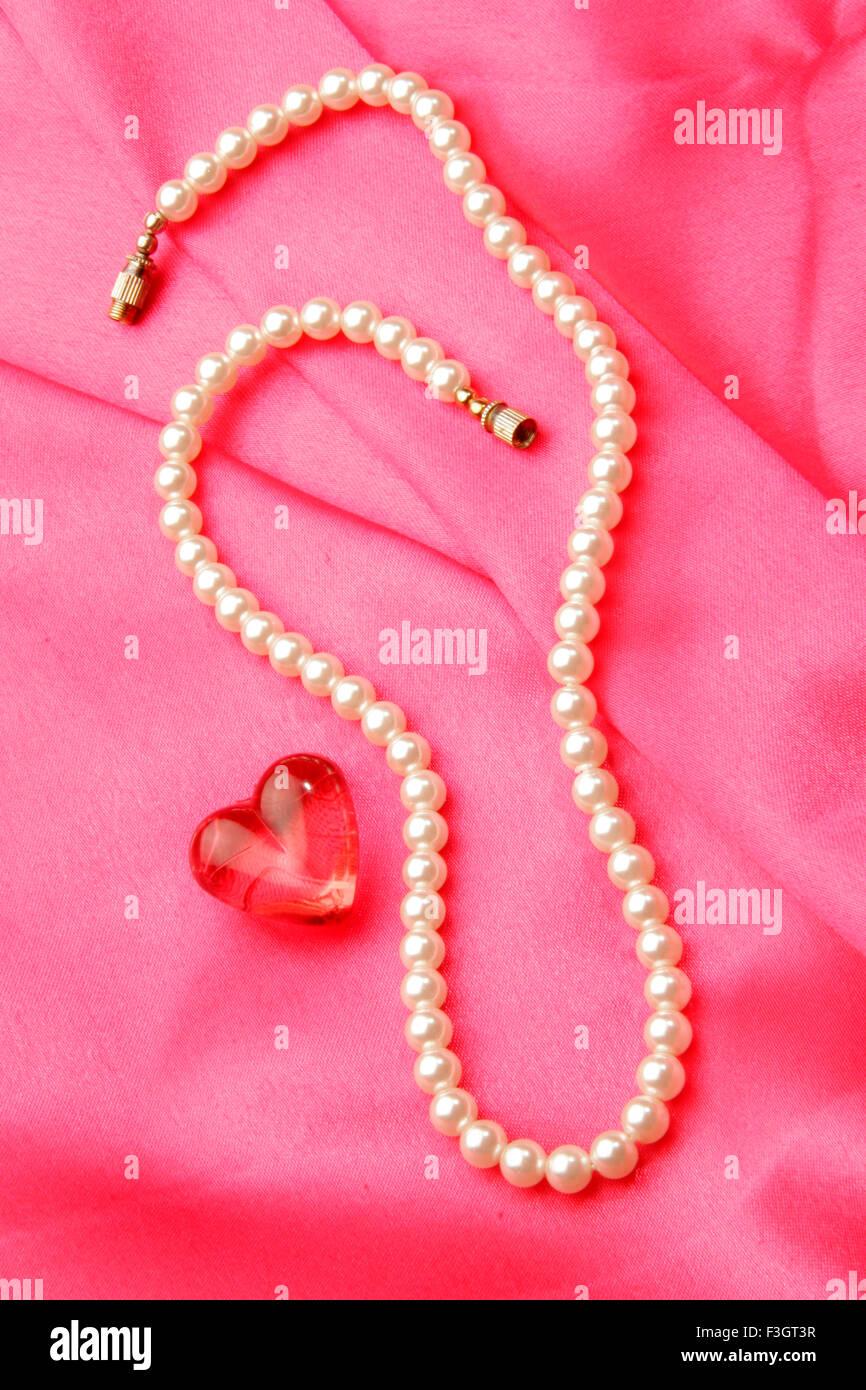 Collar de perlas en forma de joyas con piedras preciosas de color rojo sintético de forma corazón contra Imagen De Stock