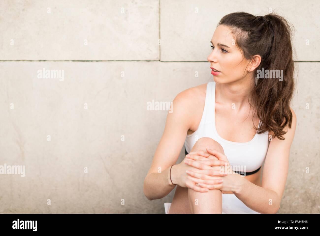 Corredoras jóvenes contra la pared inclinada mirando lateralmente Imagen De Stock
