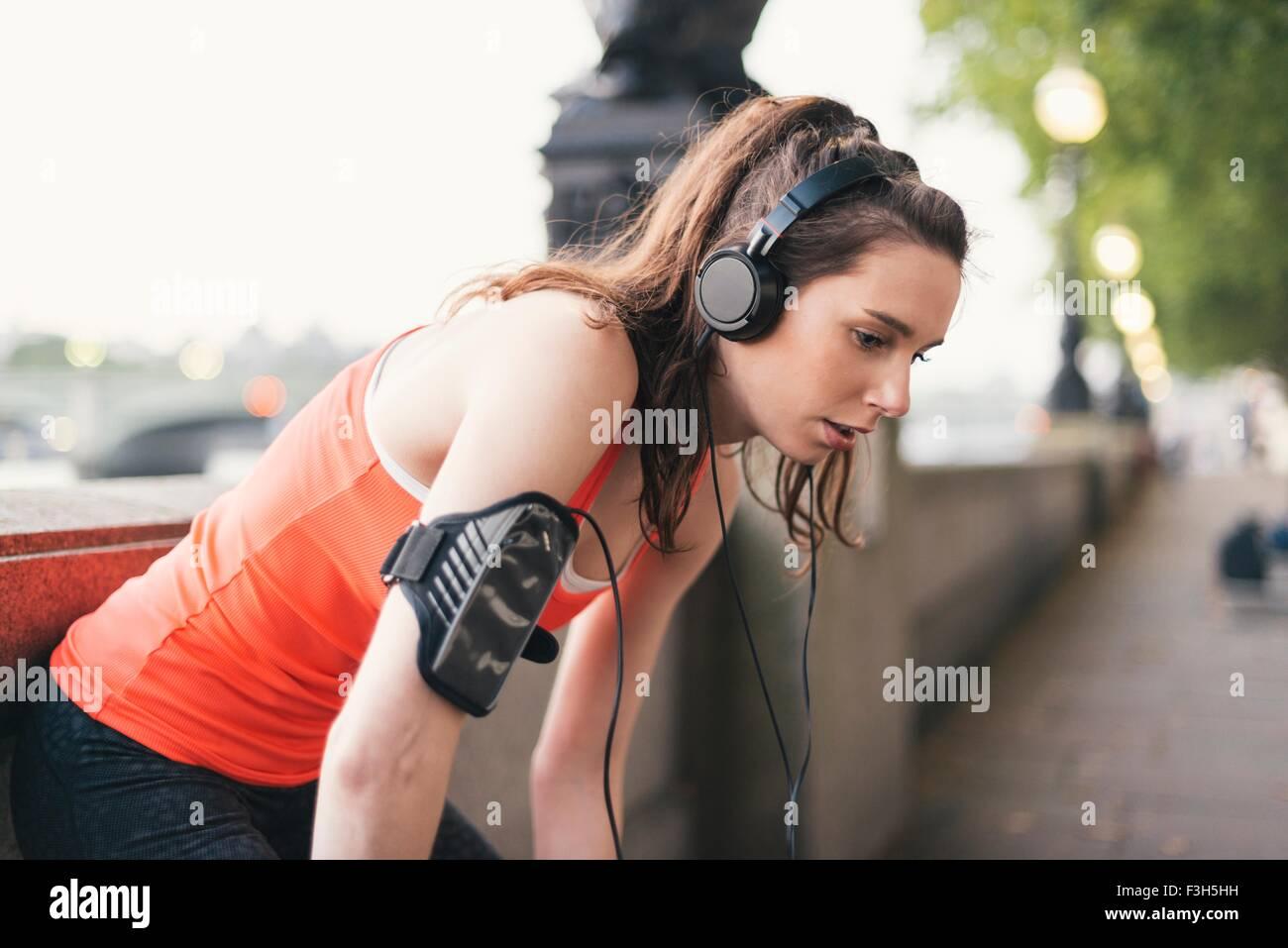 Agotado corredoras usando audífonos tomando un descanso en el Riverside Imagen De Stock
