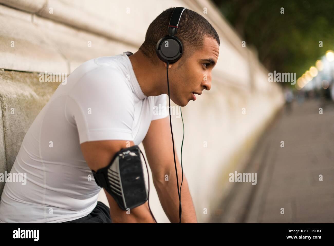 Agotado runner macho usando audífonos tomando un descanso en el Riverside Imagen De Stock