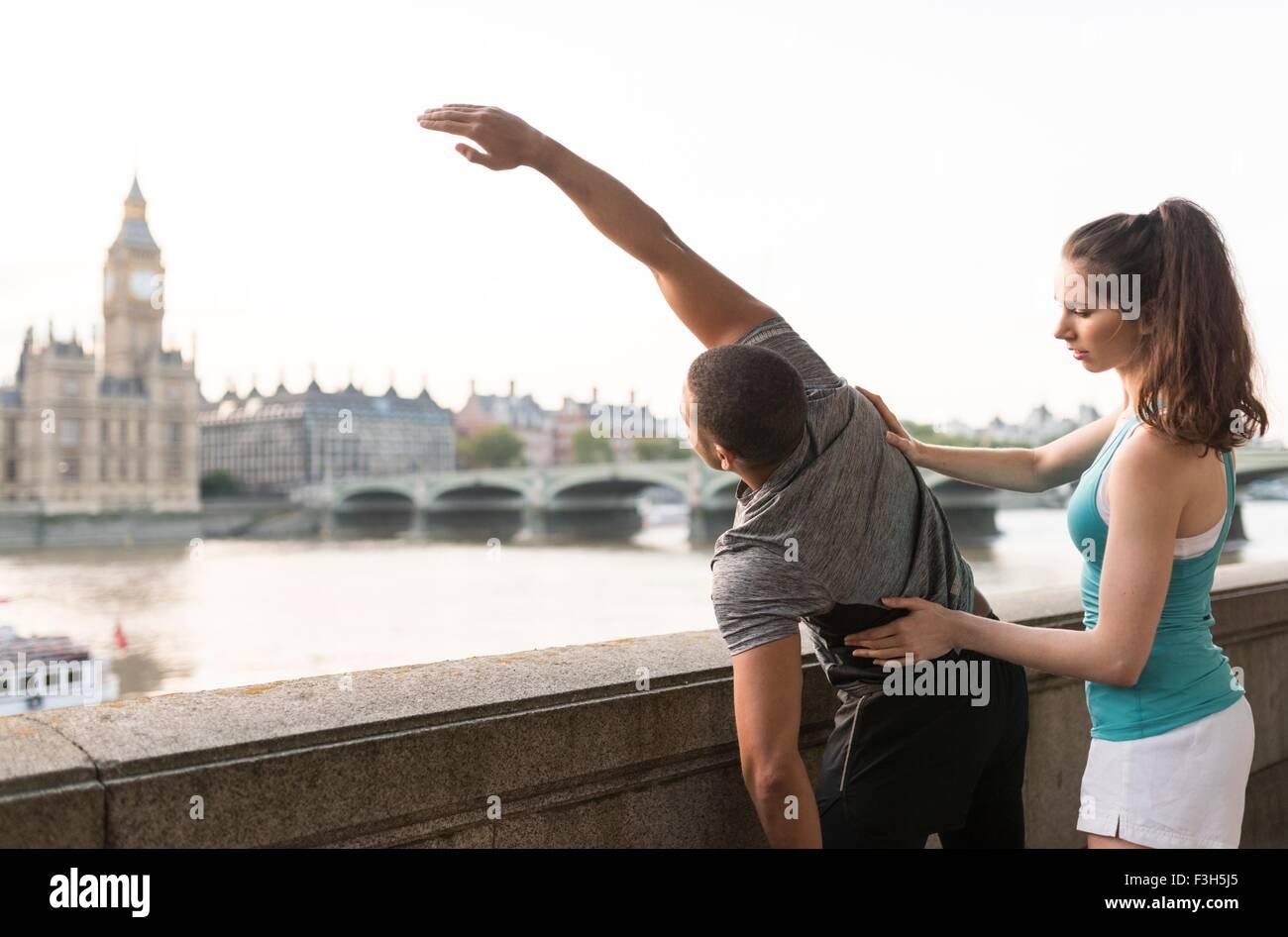 Los corredores masculinos y femeninos del calentamiento en Southbank, Londres, Reino Unido. Imagen De Stock