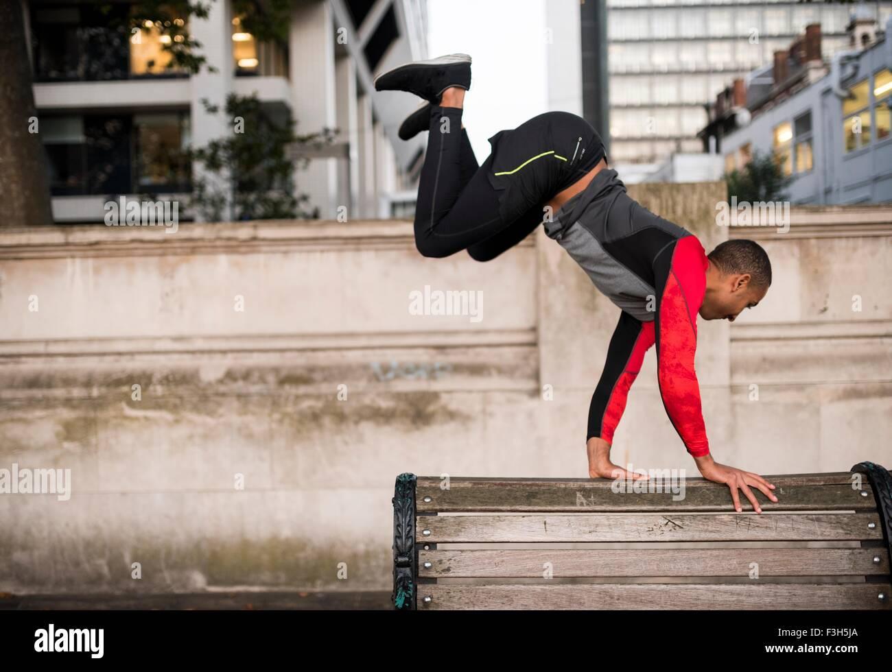 Joven saltando sobre un banco del parque en la ciudad Imagen De Stock