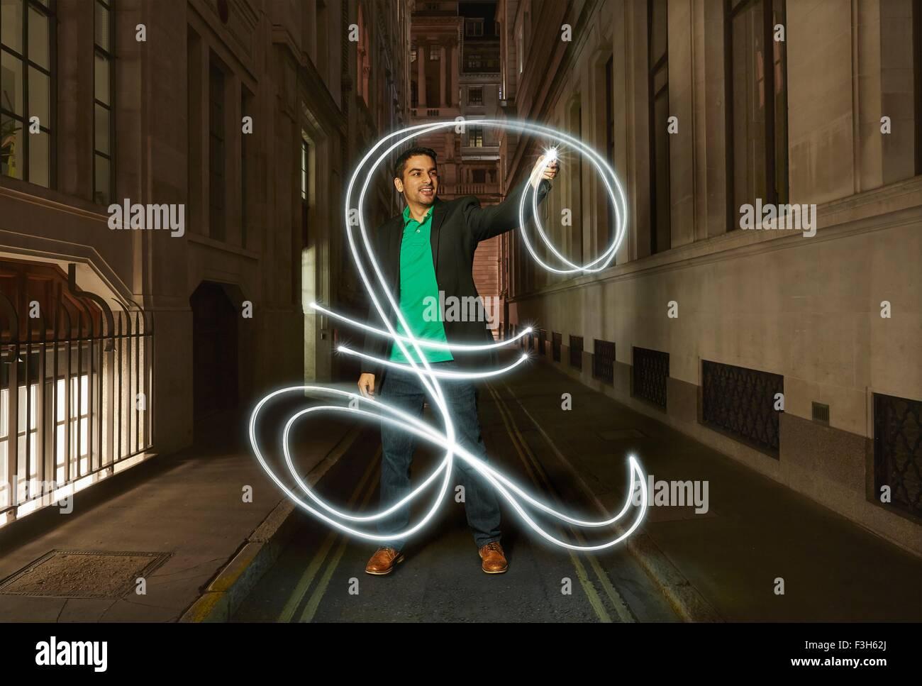 Empresario pintura luz resplandeciente signo de libra en las calles de la ciudad en la noche Imagen De Stock
