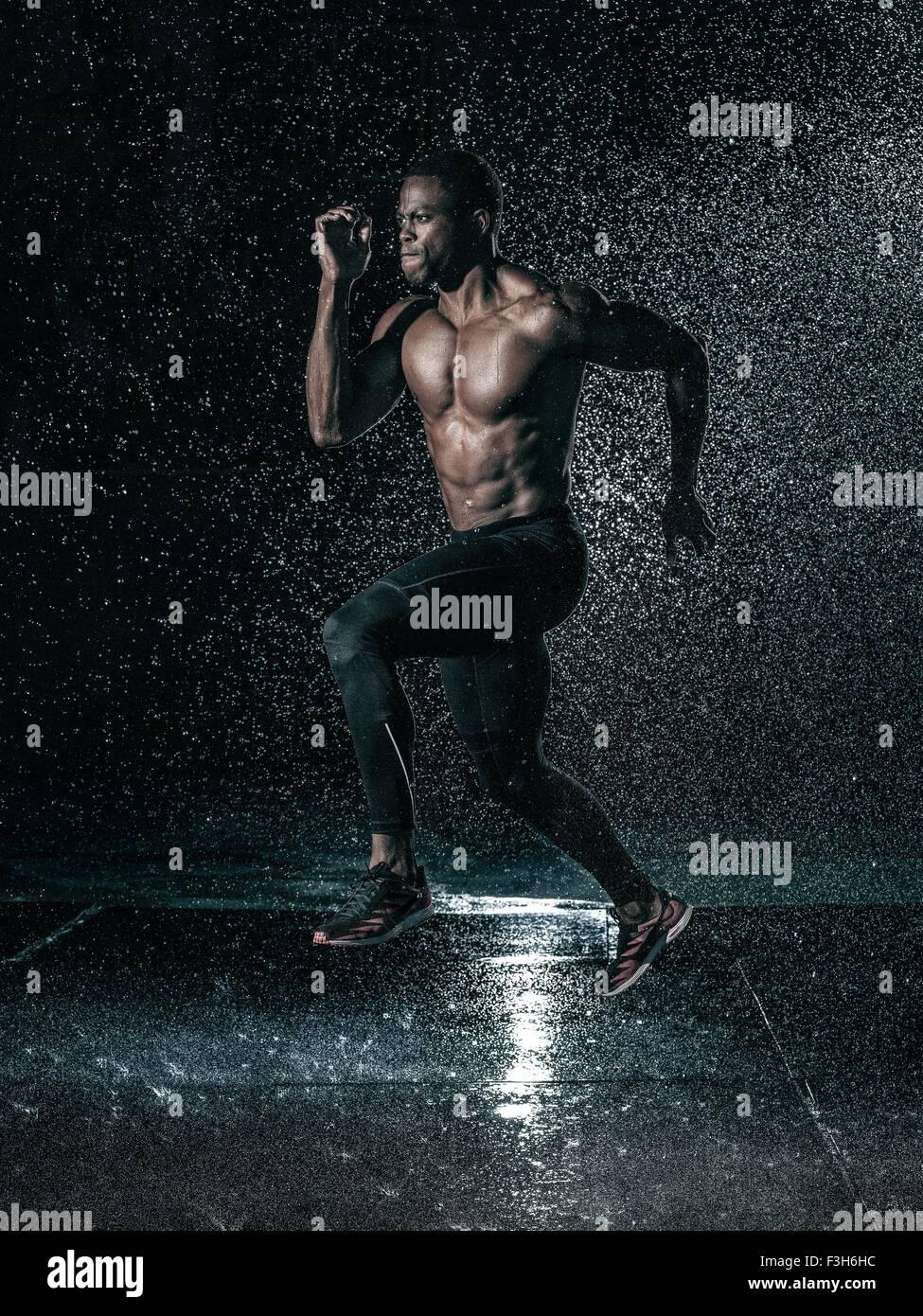Mitad hombre adulto, al aire libre, corriendo en la lluvia Imagen De Stock