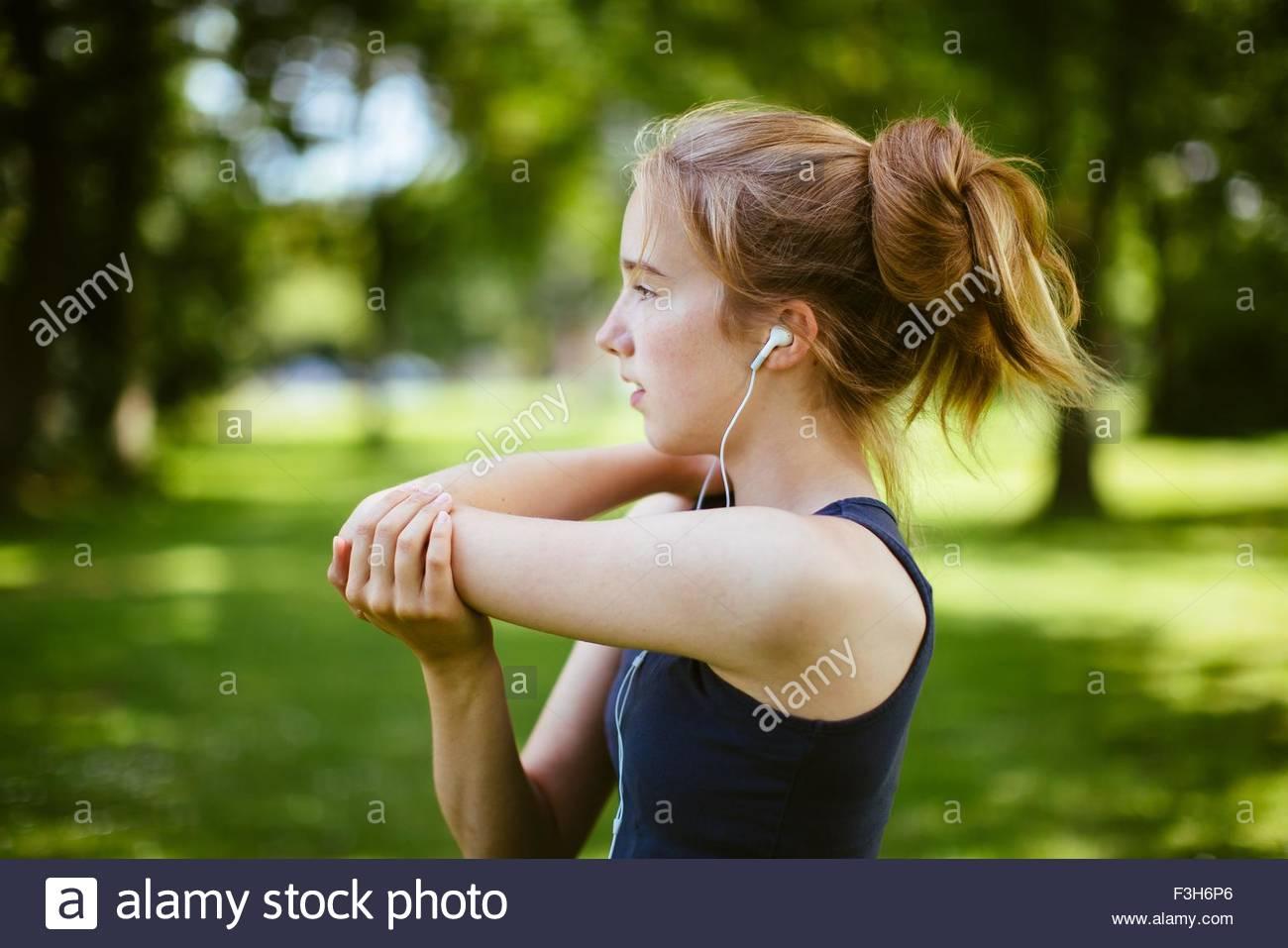 Niña en el parque, haciendo estiramientos del brazo Imagen De Stock