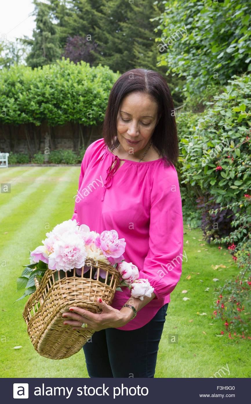 Mujer Senior recoger flores en el jardín Imagen De Stock