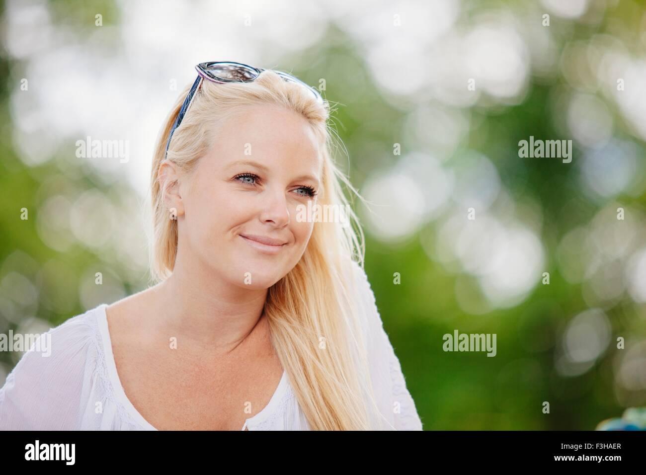 Retrato de mujer joven rubia de cabellos largos con gafas de sol sobre la cabeza mirando lejos sonriendo Imagen De Stock