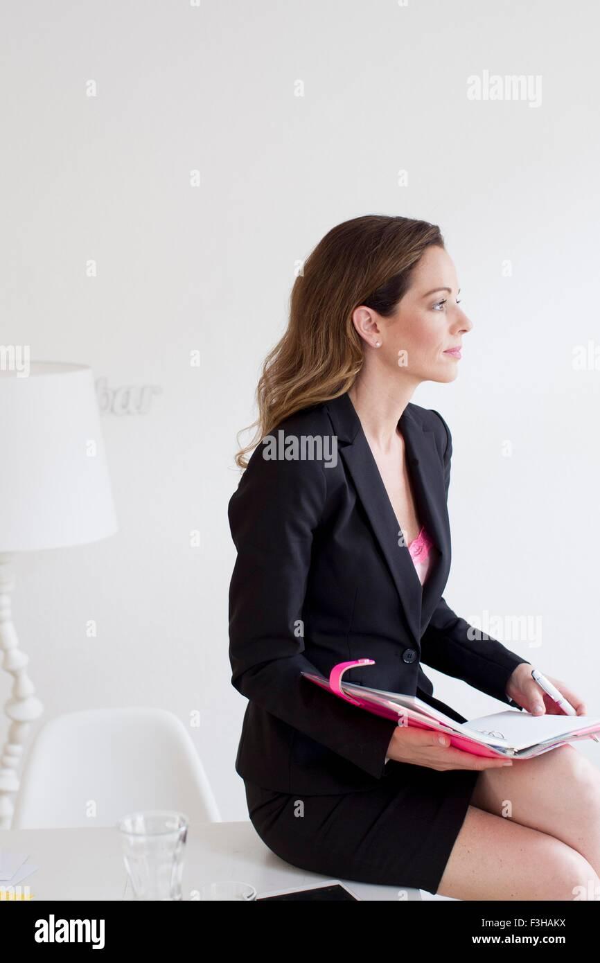 Vista lateral de la mujer madura, vistiendo trajes de negocios la celebración de archivo en busca de distancia Imagen De Stock
