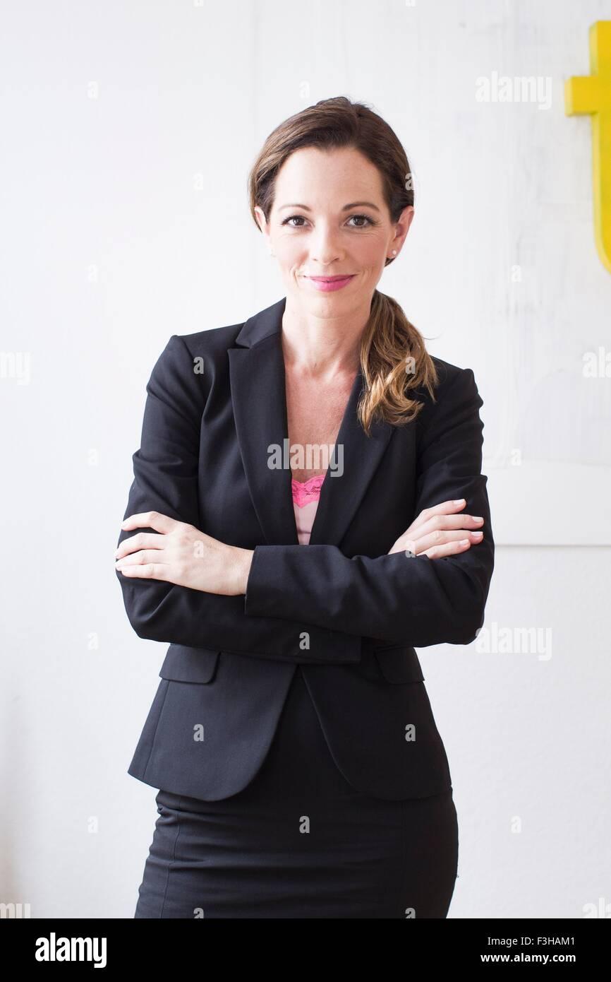 Mujer madura, vistiendo trajes de negocios con los brazos cruzados mirando a la cámara sonriendo Imagen De Stock
