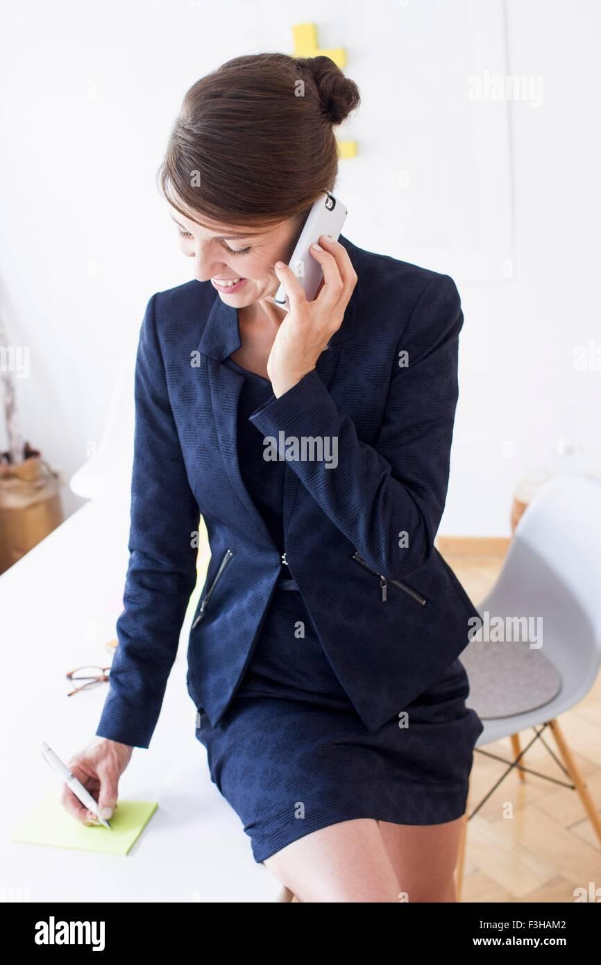 Mujer madura, vistiendo trajes de negocios utilizando el smartphone sonriendo mirando hacia abajo Imagen De Stock