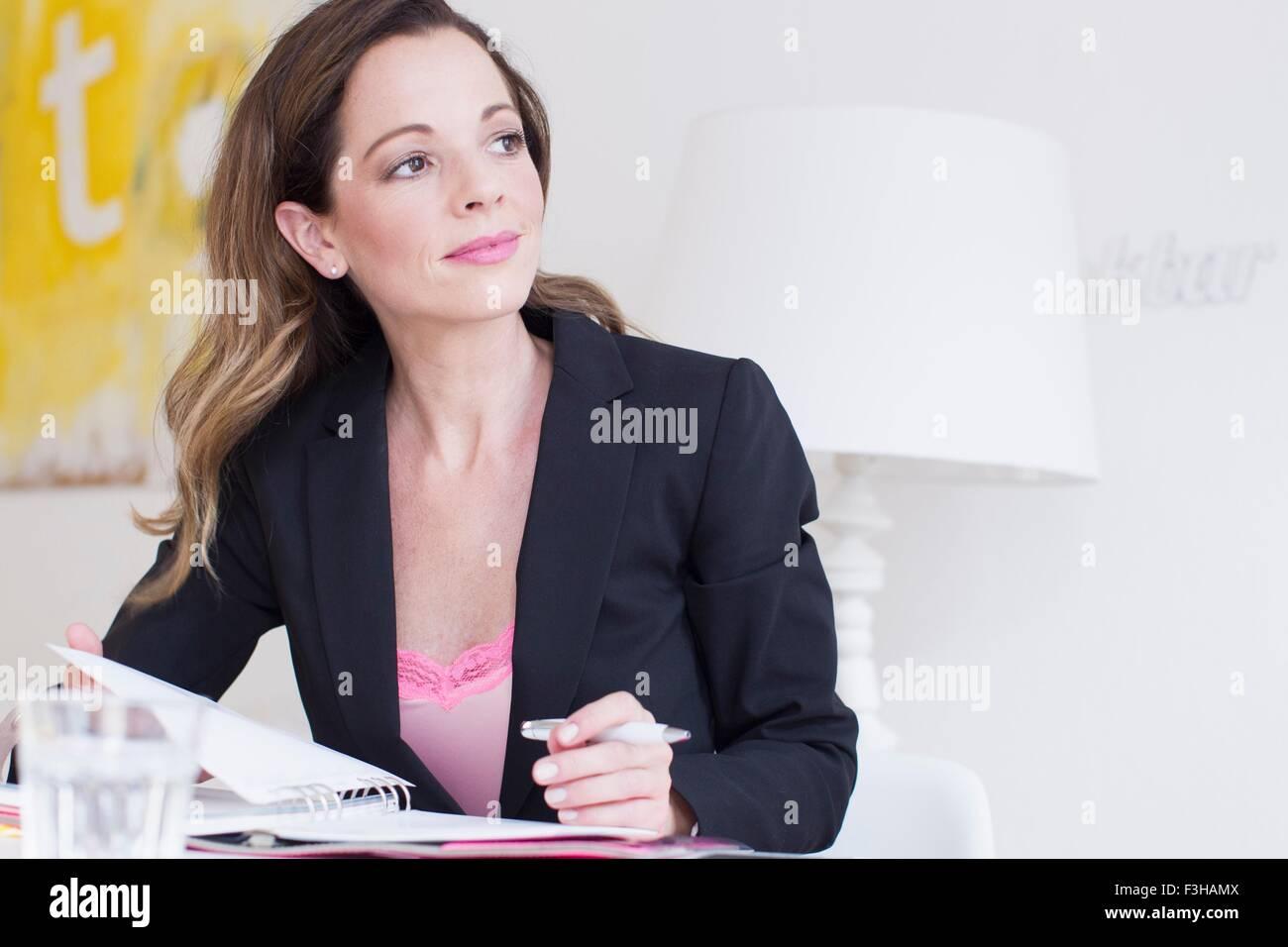 Mujer madura, vistiendo trajes de negocios sosteniendo pen y el papeleo apartar la mirada sonriendo Imagen De Stock