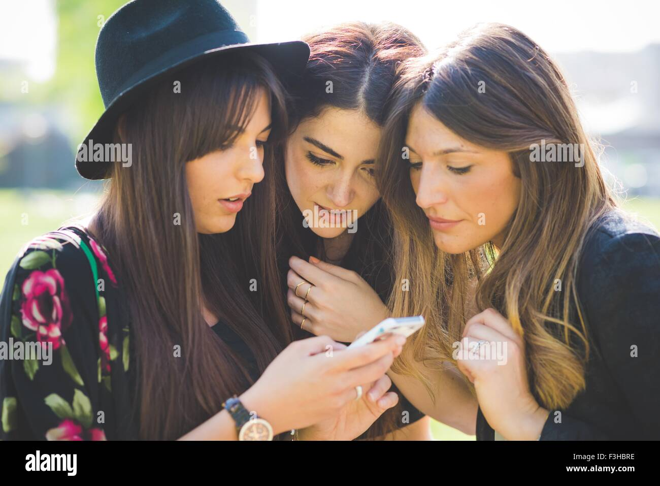 Tres jóvenes amigas huddling compartir mensajes de texto smartphone Imagen De Stock